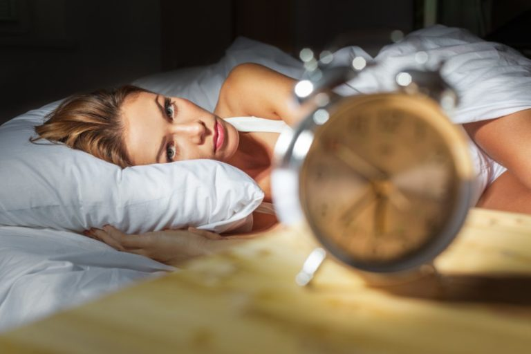 awake woman in bed on insomnia hypnosis page